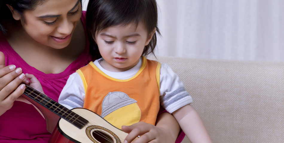 A mom is teaching her daughter to play the guitar