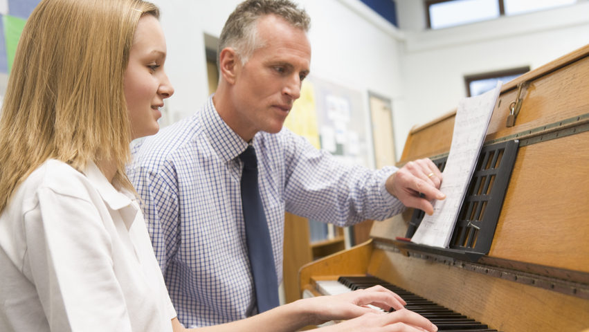 Teacher instructing adult student on playing the piano