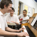 Students playing various instruments in a classroom